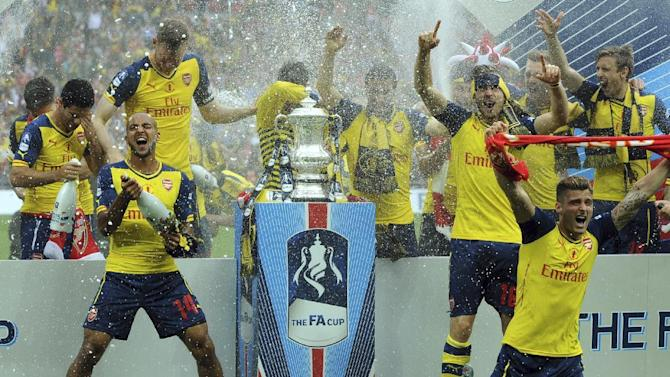 Arsenal players Theo Walcott, front left, and Olivier Giroud, right, and Aaron Ramsey, 2nd right, celebrate with team mates after winning the FA Cup final by beating Aston Villa 4-0 during the English FA Cup Final soccer match between Aston Villa and Arsenal at Wembley stadium, London, Saturday, May 30, 2015. (AP Photo/Rui Vieira)