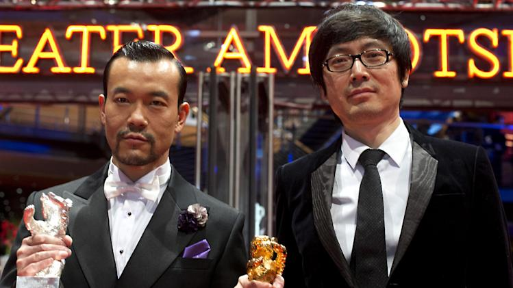 Actor Liao Fan, left, with the Silver Bear for Best Actor and director Diao Yinan with the Golden Bear for Best Film for the movie Black Coal, Thin Ice pose for photographers after the award ceremony at the International Film Festival Berlinale in Berlin, Saturday, Feb. 15, 2014. (AP Photo/Axel Schmidt)