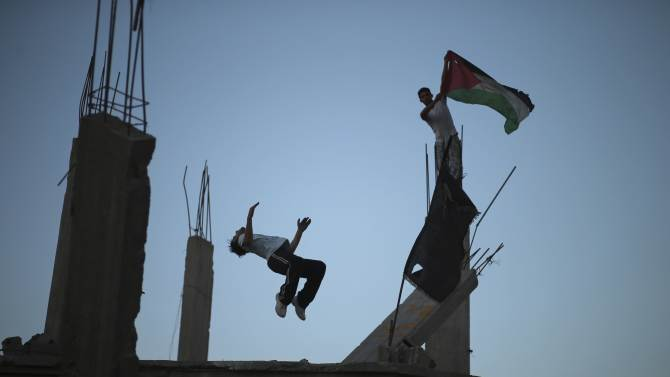A Palestinian youth holds a Palestinian flag as his another practises Parkour skills over the ruins of house in the Shejaia neighborhood east of Gaza City