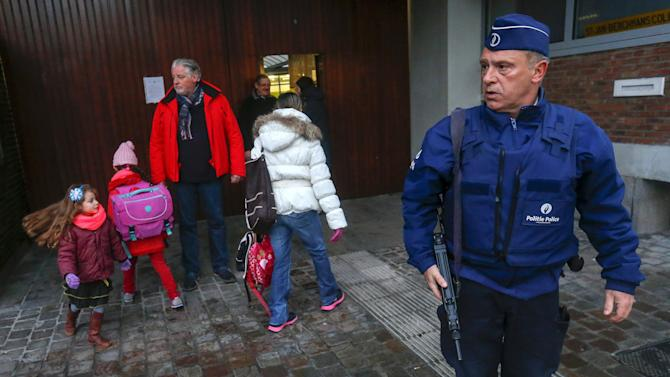 A Belgian police officer stands guard outside a school in central Brussels