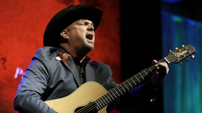 """FILE - This Oct. 7, 2012 photo shows Garth Brooks singing """"Papa Loved Mama,"""" a song written by Kim Williams, as Williams is inducted into the Nashville Songwriters Hall of Fame in Nashville, Tenn. On Sunday, Oct. 21, Brooks will be inducted into the Country Music Hall of Fame.  (AP Photo/Mark Humphrey, file)"""