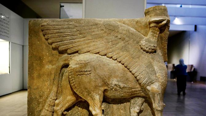 This Monday, Sept. 15, 2014 photo shows a winged bull made out of limestone displayed at the Iraqi National Museum in Baghdad. Now much of that archaeological wealth is under the control of extremists from the Islamic State group. They have already destroyed some of that heritage in their zealotry to uproot what they see as heresy. Antiquities officials in Iraq and Syria warn of a disaster as the region's history is erased. (AP Photo/Hadi Mizban)