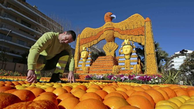 "A worker puts the final touch to a replica of a giant eagle and pharaons made with lemons and oranges which shows a scene of the movie ""Cleopatra"" during the Lemon festival in Menton"