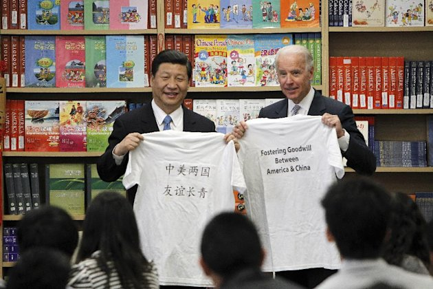Chinese Vice President Xi Jinping and Vice President Joe Biden hold t-shirts given to them by students during their visit to the International Studies Learning Center in South Gate, Calif., Friday, Fe