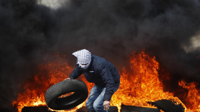 A Palestinian man burns tires during a protest to support Palestinian prisoners, outside Ofer, an Israeli military prison, near the West Bank city of Ramallah, Monday, Feb. 25, 2013. The fate of the prisoners is sensitive in Palestinian society, where virtually every family has had a member imprisoned by Israel. Detainees are held on a range of charges, from stone-throwing to deadly attacks, and are seen as heroes resisting occupation. Israelis tend to view them as terrorists. (AP Photo/Majdi Mohammed)