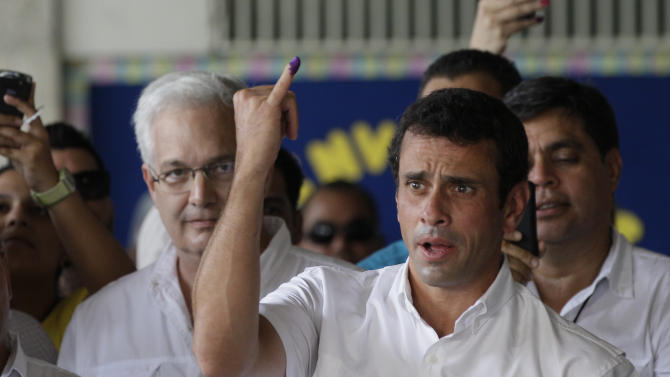 Opposition presidential candidate Henrique Capriles shows his inked pinky finger, which means he voted, at a polling station during the presidential election in Caracas, Venezuela, Sunday, Oct. 7, 2012. Capriles is running against President Hugo Chavez. (AP Photo/Ariana Cubillos)