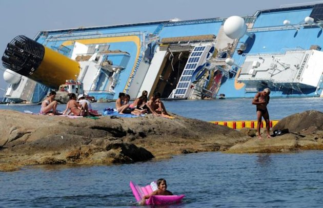 Turisti fanno il bagno di fronte alla Costa Concordia