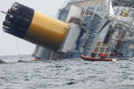 An Italian Coast Guard dinghy sails around the grounded cruise ship Costa Concordia off the Tuscan island of Giglio, Italy, Sunday, Jan. 29, 2012. Rough seas off the Tuscan coast have delayed for a second day the start of operations to remove half a million gallons of fuel from the grounded Costa Concordia. Officials called off both the fuel removal and search operations Sunday after determining the ship had moved 4 centimeters (an inch and a half) over six hours. (AP Photo/Pier Paolo Cito)