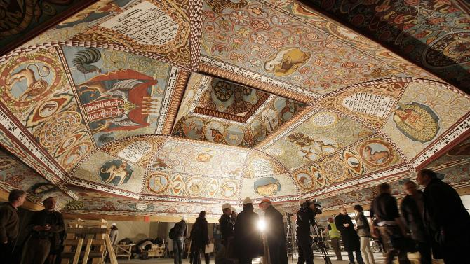 People look at the the painted ceiling of a reconstructed wooden synagogue that dates back centuries during a presentation of it to the media in Warsaw, Poland, on Tuesday March 12, 2013. The reconstructed ceiling and roof of the 17th century synagogue is a key attraction in the Museum of the History of Polish Jews, a major institution due to open next year in  Warsaw.(AP Photo/Czarek Sokolowski)