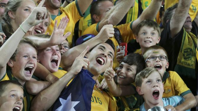 Australia's Jason Davidson poses for pictures with fans after they beat South Korea to win the Asian Cup at the Stadium Australia in Sydney