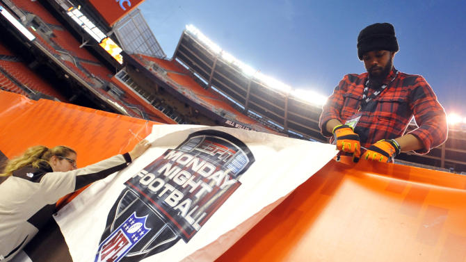 FILE - In this Nov. 3, 2015, file photo, workers install an ESPN Monday Night Football banner before an NFL football game between the Cleveland Browns and the Baltimore Ravens in Cleveland. The sports network that drives Disney's profit engine has hit a soft patch as people cut the cord to watch programming online. It's a sign of one of TV's biggest challenges: the ever-increasing cost of sports rights and whether consumers want to keep footing the bill. (AP Photo/David Richard, File)
