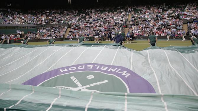 Rain covers are pulled across Centre Court during the singles match between Maria Sharapova of Russia  and Coco Vandeweghe of the United States, at the All England Lawn Tennis Championships in Wimbledon, London, Tuesday July 7, 2015. (AP Photo/Pavel Golovkin)