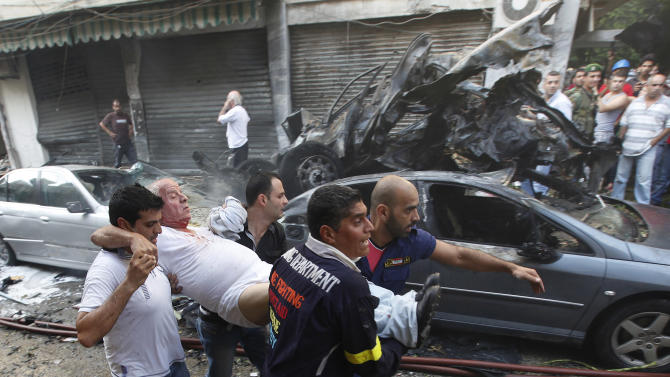 Lebanese rescue workers and civilians carry an injured man, from the scene of an explosion in the mostly Christian neighborhood of Achrafiyeh, Beirut, Lebanon, Friday Oct. 19, 2012. Lebanese Red Cross and security officials say a car bomb in east Beirut has killed at least eight people and wounded dozens in the worst blast the city has seen in years, coming at a time when Lebanon has seen a rise in tension and eruptions of clashes stemming from the civil war in neighboring Syria. (AP Photo/Hussein Malla)