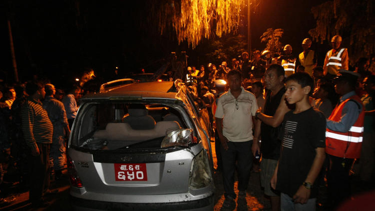 Nepalese rescue workers and people stand near a damaged car after after the British Embassy's compound wall collapsed reportedly killing three pedestrians following an earthquake in Katmandu, Nepal, Sunday, Sept. 18, 2011. A strong earthquake with a preliminary magnitude of 6.8 hit northeastern India on Sunday near the border with Nepal. Reports said several people were injured and some buildings fell in the capital of India's Sikkim state. In neighboring Nepal and Bangladesh, the quake sent residents rushing out their homes, offices and shopping centers. (AP Photo/Binod Joshi)