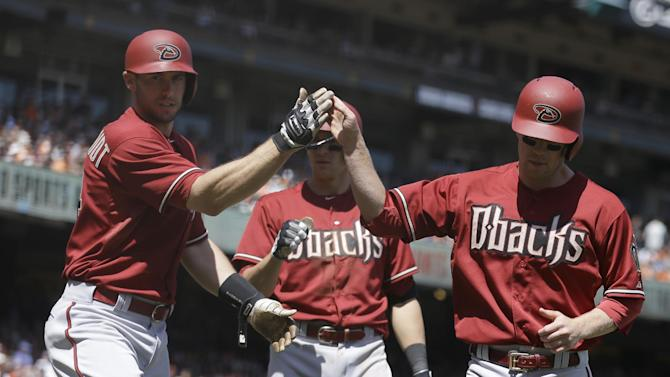 Arizona Diamondbacks' Aaron Hill, right, is congratulated by Paul Goldschmidt, left, after Hill scored against the San Francisco Giants in the third inning of a baseball game Sunday, April 19, 2015, in San Francisco. Hill scored on a single by Arizona's Chris Owings. (AP Photo/Ben Margot)