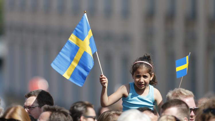 A girl waves with a Swedish flag outside the Royal castle in Stockholm, Saturday June 8, 2013 where Princess Madeleine of Sweden will marry New York banker Christopher O'Neill in the Royal church later in the day. (AP Photo / Bertil Enevåg Ericson / SCANPIX) ** SWEDEN OUT **