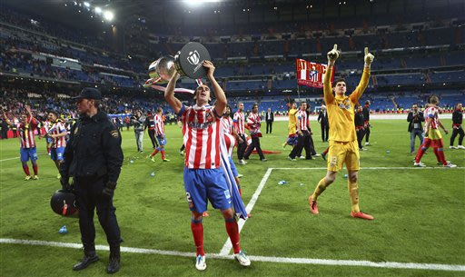 Atletico de Madrid's Diego Godin from Uruguay, holds up the trophy as he celebrates with teammates after beating Real Madrid in their Copa del Rey final soccer match at the Santiago Bernabeu stadium i