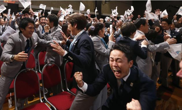 Members of the Tokyo bid committee celebrate as Jacques Rogge President of the International Olympic Committee announces Tokyo as the city to host the 2020 Summer Olympic Game during a ceremony in Bue