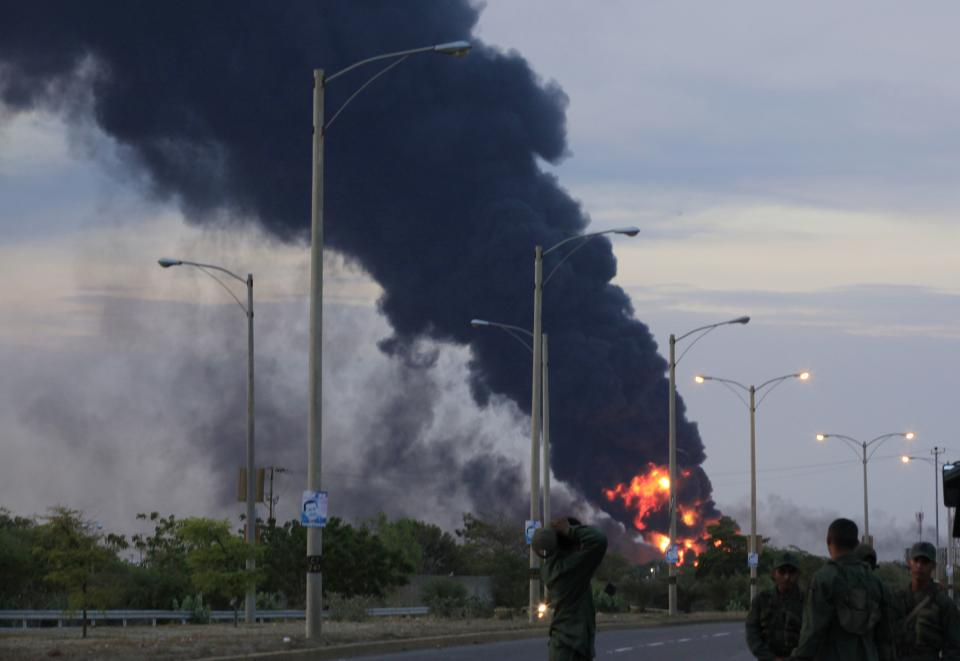Fire and smoke rise over the Amuay refinery near Punto Fijo, Venezuela, Saturday, Aug. 25, 2012. A huge explosion rocked Venezuela's biggest oil refinery, killing at least 24 people and injuring dozens, an official said. (AP Photo/Ariana Cubillos)
