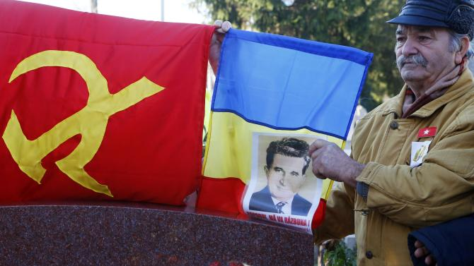 A man holds a portrait of Romania's late communist dictator Nicolae Ceausescu during a commemoration ceremony at his grave in a Bucharest cemetery