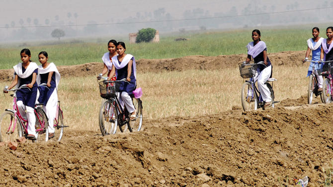 In this March 15, 2012 photo, Indian schoolgirls ride bicycles, received under a Bihar state government program of giving free bicycles to teenage girls to keep them in school, on the outskirts of Patna, India. Before starting the program in 2007, officials in Bihar, one of India's poorest and most backward states, despaired over how to educate the state's females, whose literacy rate of 53 percent is more than 20 points below that of its men. The program was an instant success, with the number of girls registered in the ninth grade in Bihar's state schools more than tripling in four years, from 175,000 to 600,000. (AP Photo/Prashant Ravi)