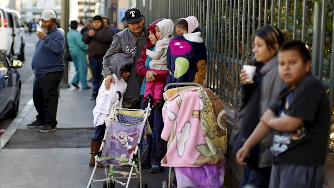People wait in line for an early Thanksgiving meal served to the homeless at the Los Angeles Mission in Los Angeles