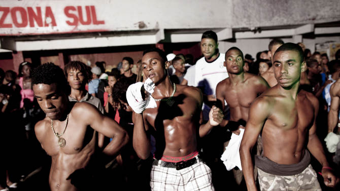 """In this Feb. 3, 2012 photo, people dance at a funk """"baile"""" in the Cantagalo slum in Rio de Janeiro, Brazil.  In the last five years, the genre has expanded its reach and enjoyed more social acceptance, with the help of an association of funk artists and supporters, Apafunk, and the backing of liberal legislators. Its market potential has become hard to ignore: A recent survey by the Brazilian think tank the Getulio Vargas Foundation found funk disc jockeys, MCs and others generate about $720 million a month in revenue. (AP Photo/Felipe Dana)"""