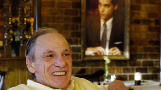 """FILE - In this Feb. 22, 2005 file photo, Henry Hill sits in the dining room of the Firefly restaurant in North Platte, Neb., with a portrait of actor Ray Liotta portraying Hill in the movie """"Goodfellas"""" hanging on the wall behind him. Hill, whose life as a mobster and FBI informant was the basis for the Martin Scorcese film, has died. Hill's girlfriend Lisa Caserta says he died in a Los Angeles hospital after a long illness. He was 69. (AP Photo/Nati Harnik, File)"""