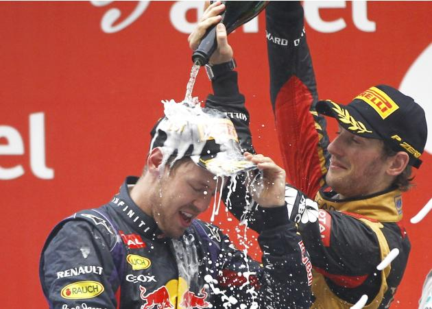 Lotus F1 Formula One driver Grosjean sprays Red Bull Formula One driver Vettel after the Indian F1 Grand Prix at the Buddh International Circuit in Greater Noida