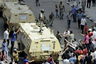 An Egyptian anti-military protester confronts an army officer following the deployment of a military unit in the Abbassiya district of Cairo