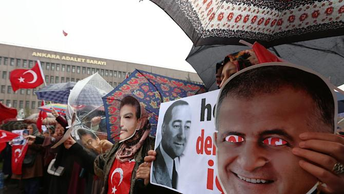 People wear masks of Ekrem Dumanli, the editor-in-chief of Zaman newspaper, as they protest against his detention in Istanbul five days ago, in Ankara, Turkey, Thursday, Dec. 18, 2014. Police conducted raids in a dozen Turkish cities Sunday, detaining at least 32 people — including journalists, TV producers and police — known to be close to a movement led by a U.S.-based moderate Islamic cleric who is a strong critic of President Recep Tayyip Erdogan. It was the latest crackdown on cleric Fethullah Gulen's movement, which the government has accused of orchestrating an alleged plot to try to bring it down. A black and white image of former prime minister Adnan Menderes is seen at the center.(AP Photo/Burhan Ozbilici)