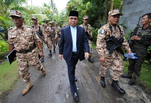 Murad Ebrahim (C), chairman of the Moro Islamic Liberation Front (MILF), with his troops at Camp Darapan on Mindanao island in 2011. The MILFS signed a historic pact with the government on Monday to end a four-decade conflict, but both sides warned the road to peace had only just begun