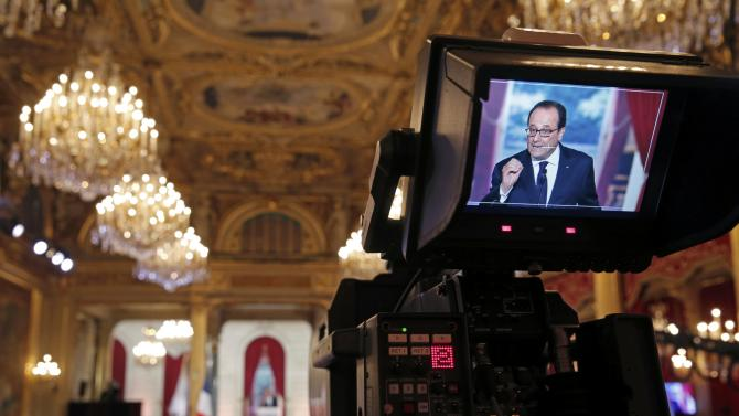 French President Hollande is seen through a video camera screen as he addresses a news conference at the Elysee Palace in Paris