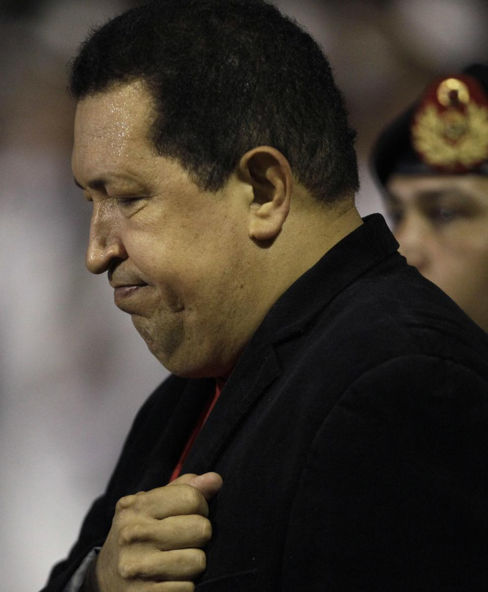 Venezuela's President Hugo Chavez places his hand over his heart upon his arrival to the Simon Bolivar airport in Maiquetia, Venezuela, Friday March 16, 2012. Chavez returned home Friday nearly three weeks after undergoing cancer surgery in Cuba. (AP Photo/Fernando Llano)
