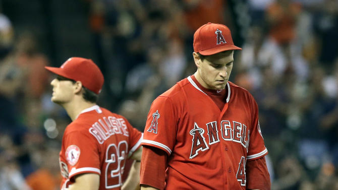 Los Angeles Angels starting pitcher Garrett Richards, right, heads back to the mound as third baseman Conor Gillaspie (22) goes back to third after Houston Astros' Jose Altuve hit an RBI-single in the fifth inning of a baseball game Wednesday, July 29, 2015, in Houston. (AP Photo/Pat Sullivan)