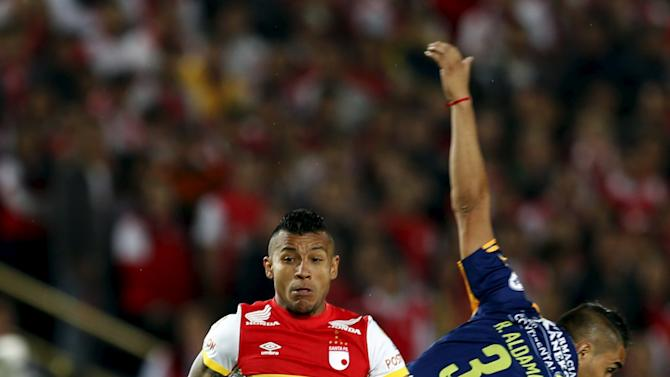 Morelo of Colombia's Santa Fe fights for the ball with Aldama of Paraguay's Sportivo Luqueno during their Copa Sudamericana match at the Campin stadium in Bogota