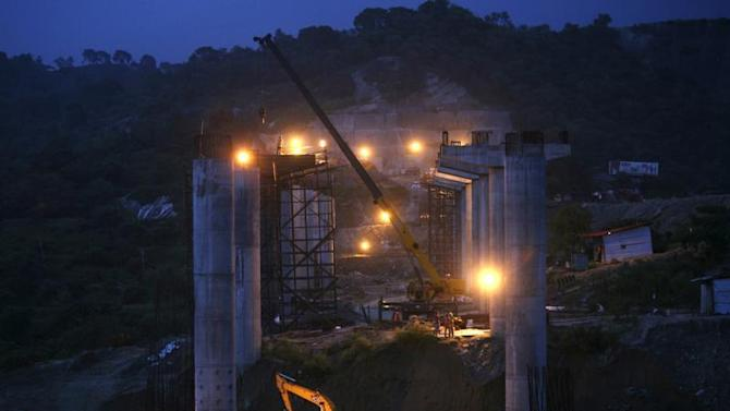 Labourers work at the construction site of a highway bridge on the outskirts of Jammu