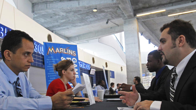 In this Wednesday, Oct. 24, 2012, file photo, Job applicant Rafael Rodriguez, right, is interviewed by Eric Ramirez, manager of game presentation and video production, at Marlins Park in Miami.  Weekly applications for U.S. unemployment aid fell last week to a seasonally adjusted 369,000, a level consistent with modest hiring. The Labor Department said Thursday, Oct. 25, 2012, that unemployment benefit applications dropped by 23,000, from a revised 392,000 the previous week. (AP Photo/Alan Diaz)