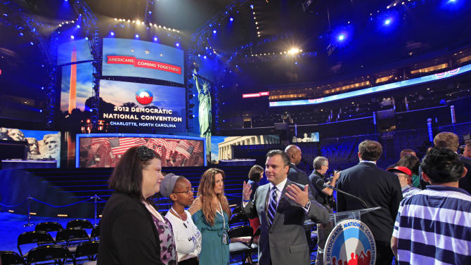 DNCC CEO Steve Kerrigan, center, talks with guests near the main stage during the public unveiling of Democratic National Convention's facilities at Time Warner Arena in Charlotte, N.C., Friday, Aug. 31, 2012. (AP Photo/Chuck Burton)