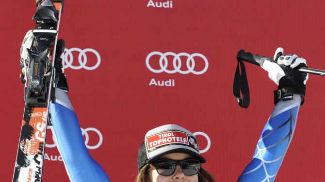 Leanne Smith, of the United States, celebrates on the podium after placing third in an Alpine Ski World Cup women's downhill, in Cortina D'Ampezzo, Italy, Saturday, Jan.19, 2013. (AP Photo/Giovanni Auletta)