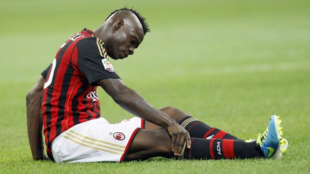 AC Milan's Mario Balotelli touch his knee as he sits on the pitch during the match against Napoli in their Italian Serie A soccer match at the San Siro stadium in Milan September 22, 2013 (Reuters)