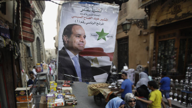 """Egyptian shoppers walk under a poster supporting presidential candidate Abdel-Fattah el-Sissi, the country's former military chief, in Cairo, Egypt, Saturday, May 24, 2014. Considered all but certain to win is el-Sissi, the man who removed the former president, Mohammed Morsi. El-Sissi, who for the past 10 months has been the most powerful figure in Egypt, faces one other candidate in the race, leftist politician Hamdeen Sabahi, who finished third in the 2012 presidential election. Arabic reads, """"Abdel-Fattah el-Sissi, presidential candidate number 1."""" (AP Photo/Amr Nabil)"""