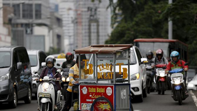 A vendor pushes his fried tofu cart across a busy street in Jakarta