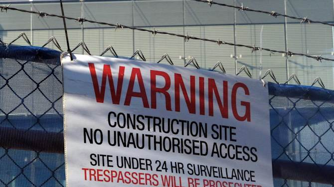 A warning sign hangs on a fence enclosing the Australian Security Intelligence Organization's new headquarters under construction in Canberra, Australia, Tuesday, May 28, 2013. Australian officials have refused to confirm or deny whether Chinese hackers had stolen the blueprints of the new spy agency building as a news report claims. (AP Photo/Rod McGuirk)