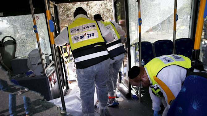 Members of Zaka Rescue and Recovery team stand beside a covered body aboard a bus, after an attack in Jerusalem