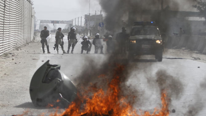 Afghan police stand by burning tires during a protest, in Kabul, Afghanistan, Monday, Sept. 17, 2012. Hundreds of Afghans burned cars and threw rocks at a U.S. military base as a demonstration against an anti-Islam film that ridicules the Prophet Muhammad turned violent in the Afghan capital early Monday. (AP Photo/Ahmad Jamshid)