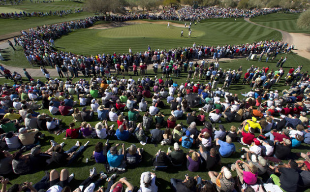 Phil Mickelson walks into the second green, which was surrounded by a large gallery, during the second round of the Phoenix Open golf tournament Friday, Feb. 1, 2013, in Scottsdale, Ariz. (AP Photo/Th