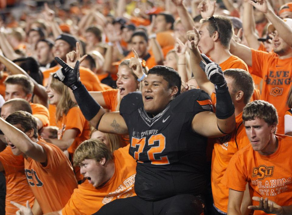 Oklahoma State defensive tackle Christian Littlehead celebrates with fans at the end of the game after Oklahoma State defeated Arizona 37-14 in an NCAA college football game in Stillwater, Okla., Thursday, Sept. 8, 2011. (AP Photo/Sue Ogrocki)