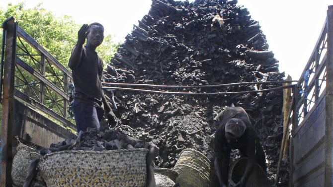 """In this photo of Tuesday Oct. 30, 2012, Somali porters  offload charcoal from a truck  at a charcoal market in Mogadishu, Somalia. Thousands of sacks of dark charcoal sit atop one another in Somalia's southern port city of Kismayo, an industry once worth some $25 million dollar a year to the al-Qaida-linked insurgents who controlled the region.  The good news sitting in the idle pile of sacks is that al-Shabab militants can no longer fund their insurgency through the illegal export of the charcoal. Kenyan troops late last month invaded Kismayo and forced out the insurgents, putting a halt to the export of charcoal, a trade the U.N. banned earlier this year in an effort to cut militant profits. The loss of the charcoal trade """"will cut a major source of revenue and thus will have a detrimental effect on their operational capacity to carry out large scale attacks,"""" Mohamed Sheikh Abdi, a Somali political analyst, said of al-Shabab.  But the flip side to the charcoal problem is that residents who made their living from the trade no longer are making money, a potentially tricky issue for the Kenyan troops who now control the region. (AP Photo/Farah Abdi Warsameh)"""