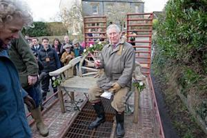 Britain's Prince Charles sits on a decorated garden bench as he travels in a trailer through flood water in Muchelney